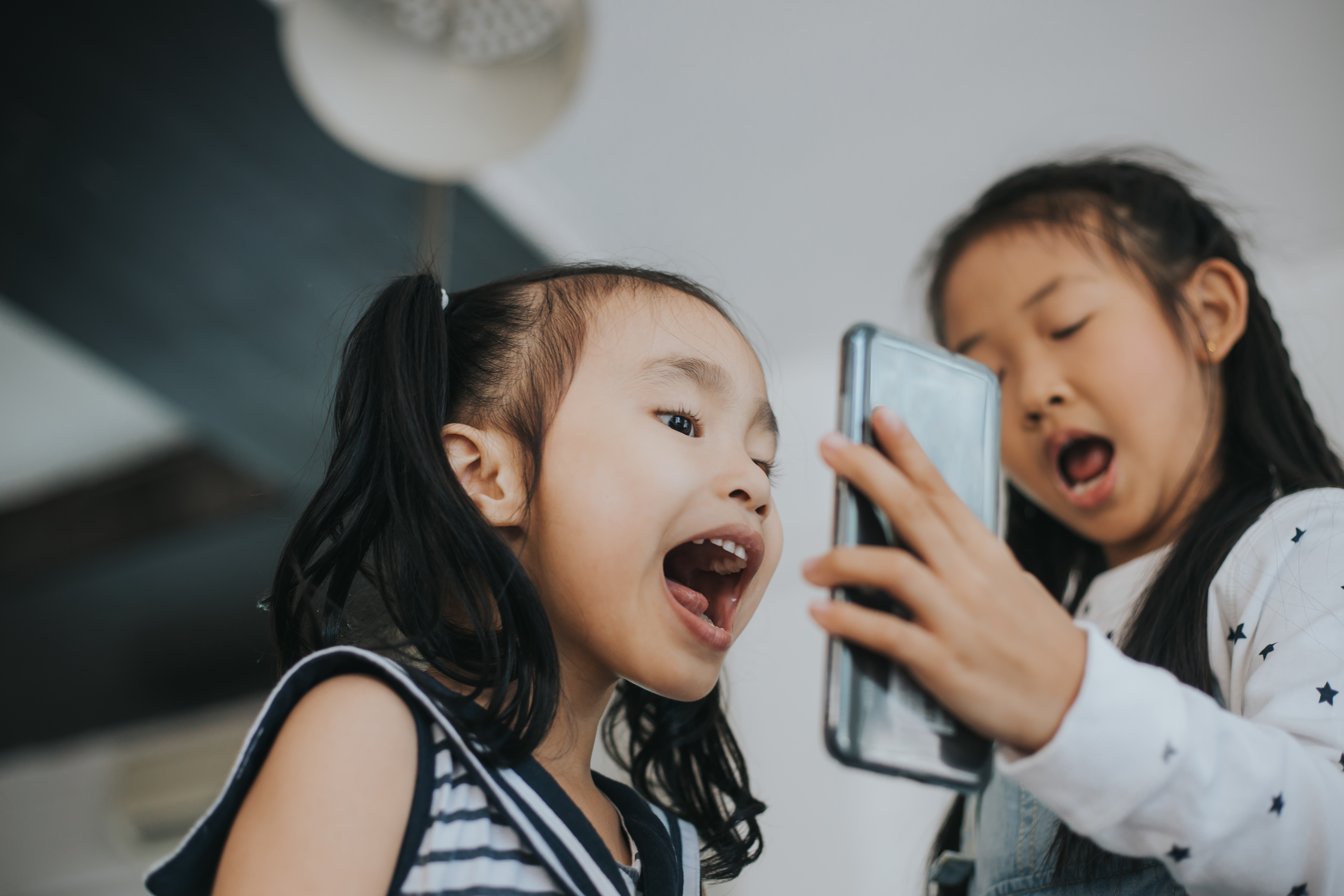 Two little girls excited, FaceTiming on cell phone