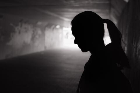 woman standing in a dark alley
